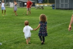 Two children walking hand in hand at AIM Services Croquet on the Green event
