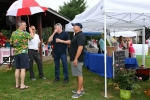 Group of men standing around with an umbrella at AIM Services Croquet on the Green event