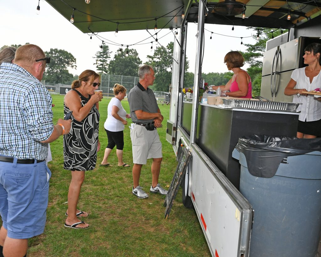 People getting food from deliciously different at AIM services Croquet on the Green event