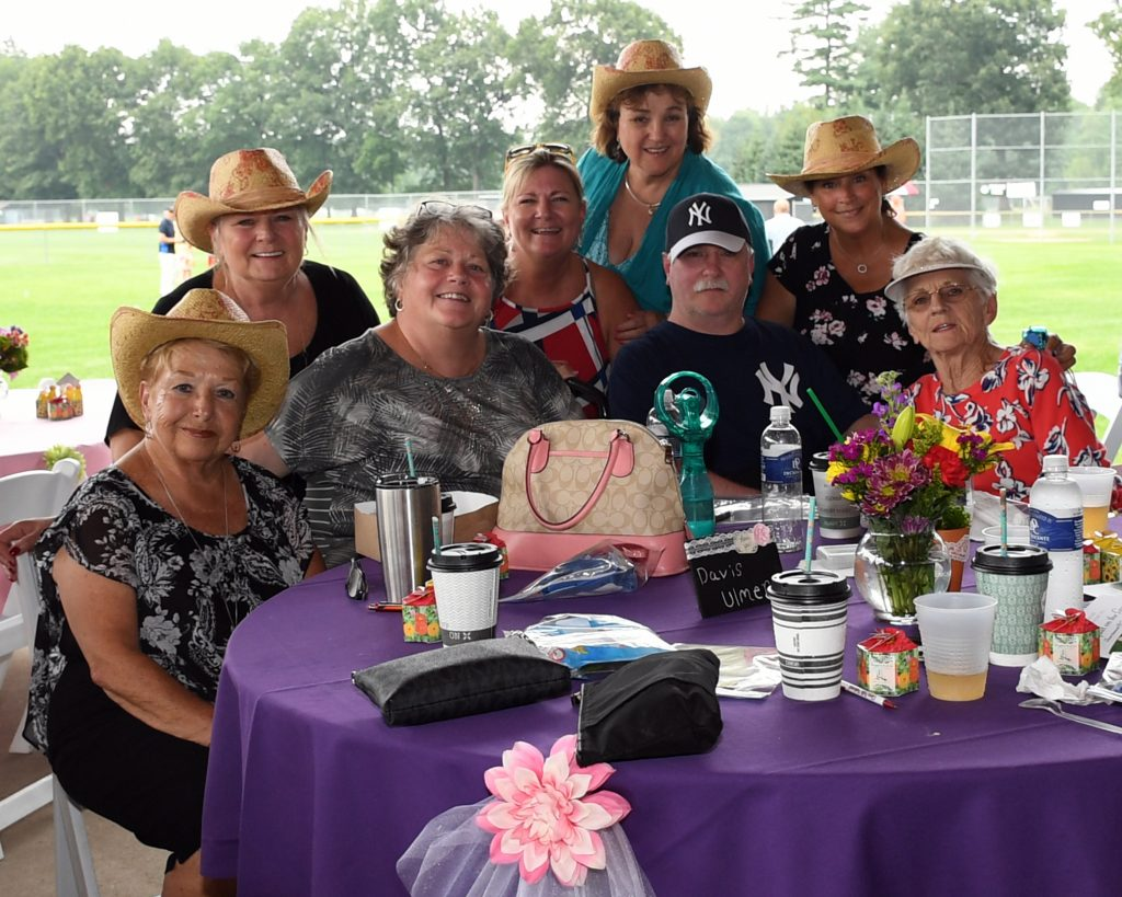 Group of eight people, some with cowgirl hats on, around a table at AIM Services Croquet on the Green event