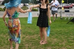 Woman handing off prize for best hat at AIM Services Croquet on the Green event
