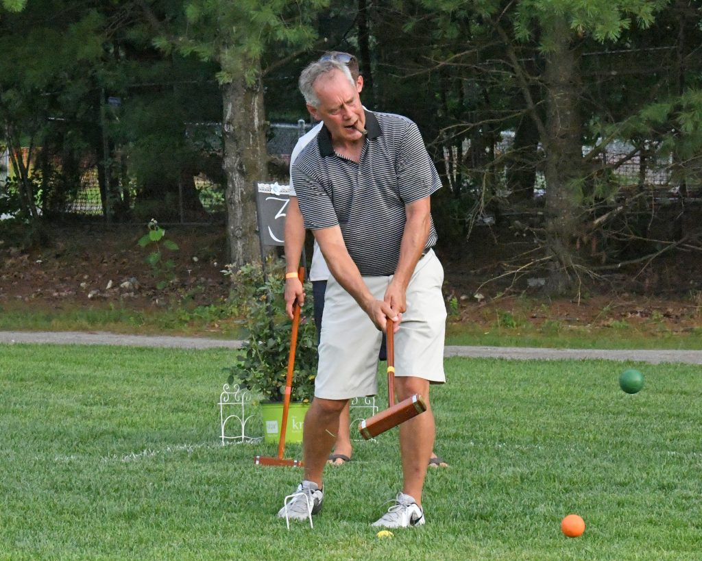 Man with cigar in his mouth taking a shot at AIM Services Croquet on the Green event