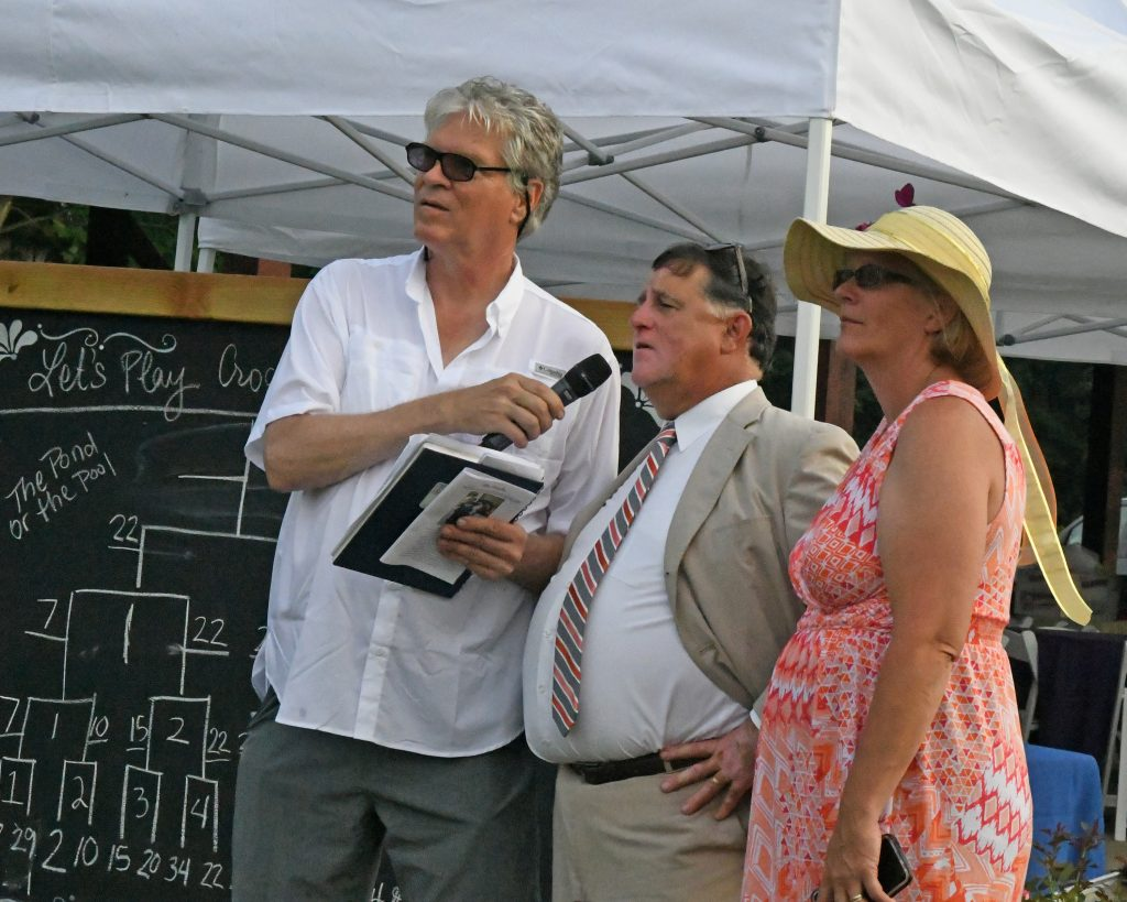 Chris Lyons commenting on Croquet game with Walt Adams and BJ Lent standing next to him at AIM Services Croquet on the Green event