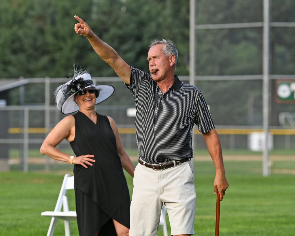 Man with cigar in mouth pointing up to the sky with woman laughing behind him at AIM Services Croquet on the Green event