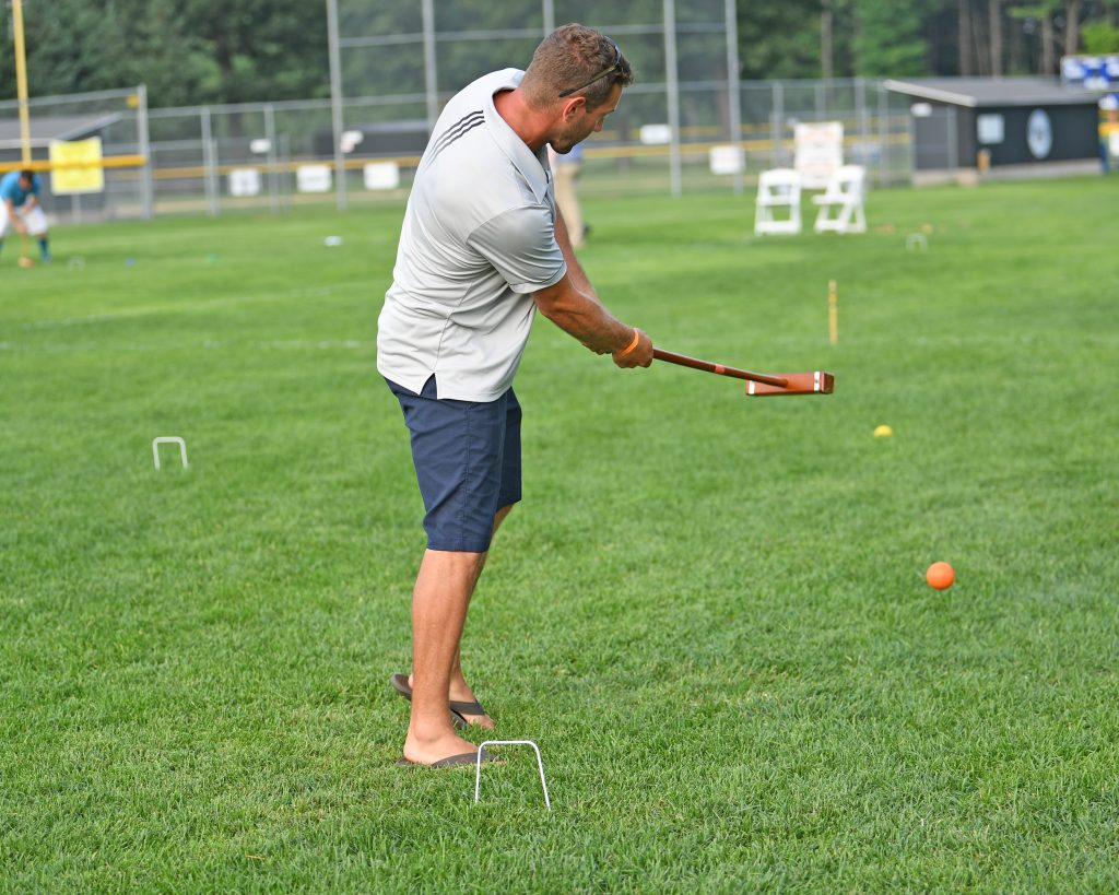 Man taking swing with mallet at AIM Services Croquet on the Green event