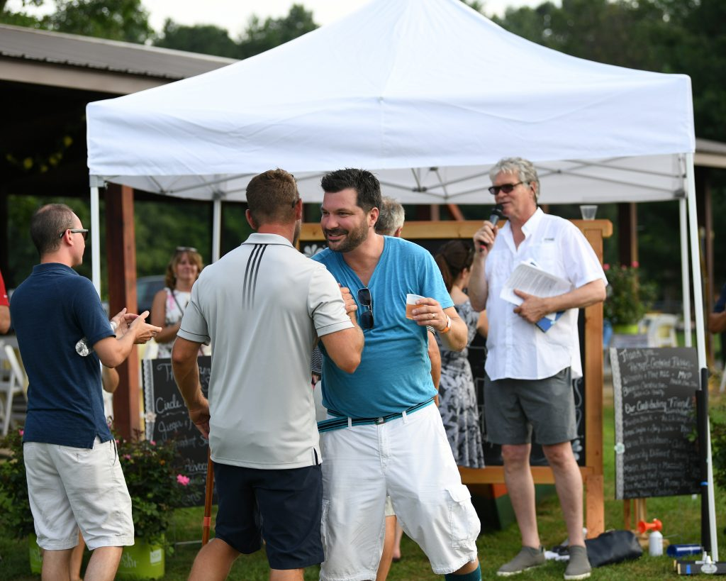 Two men shaking hands at AIM Services Croquet on the Green event