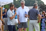 Croquet winner making comments into microphone with crowd around at AIM Services Croquet on the Green event