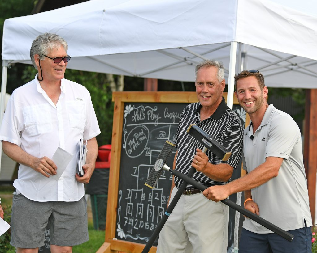 Croquet winners, father and son, pose with mallets at AIM Services Croquet on the Green event