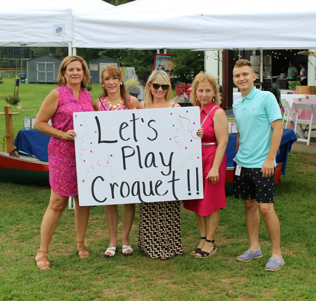group of poeple holding a sign that says let's play croquet!!