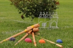 Croquet mallets and balls laying on the ground at AIM Services Croquet on the Green event