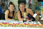 Two woman smiling at table with flower boxes at AIM Services Croquet on the Green event