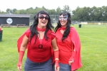 Two woman in superhero costumes laughing at AIM Services Croquet on the Green event