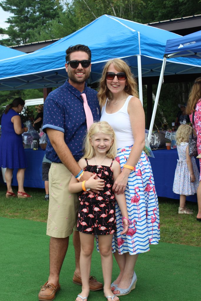 Couple with young daughter all dressed in flamingo themed clothing at AIM Services Croquet on the Green event