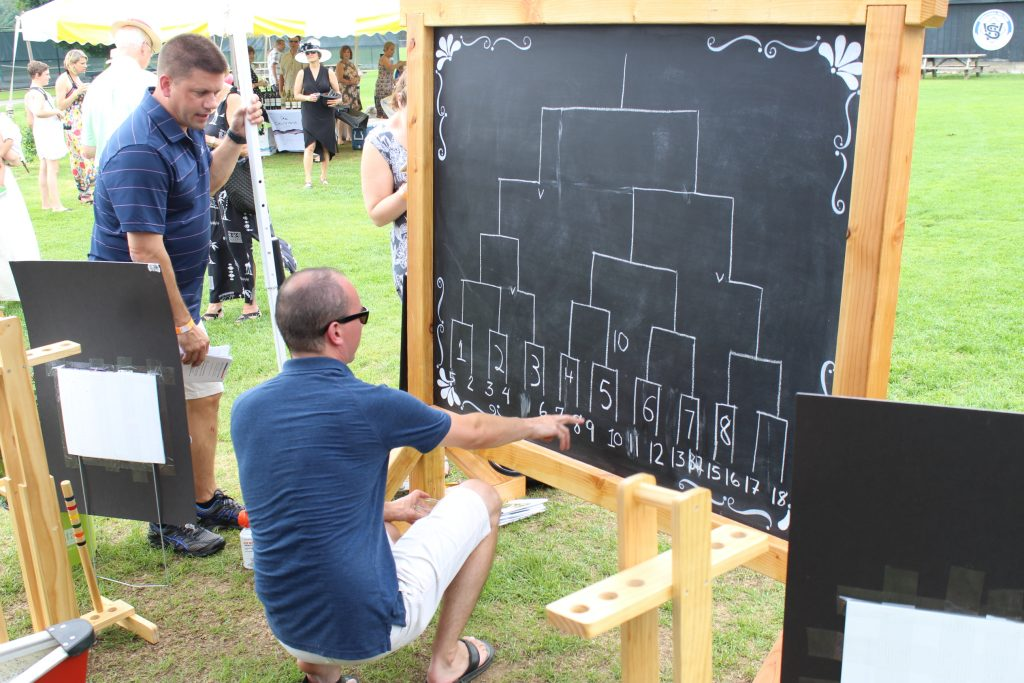 Tournament Judge writing fields on chalk board score board at AIM Services Croquet on the Green event