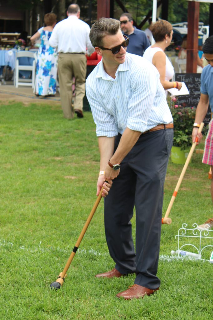 Man posing with croquet mallet at AIM Services Croquet on the Green event