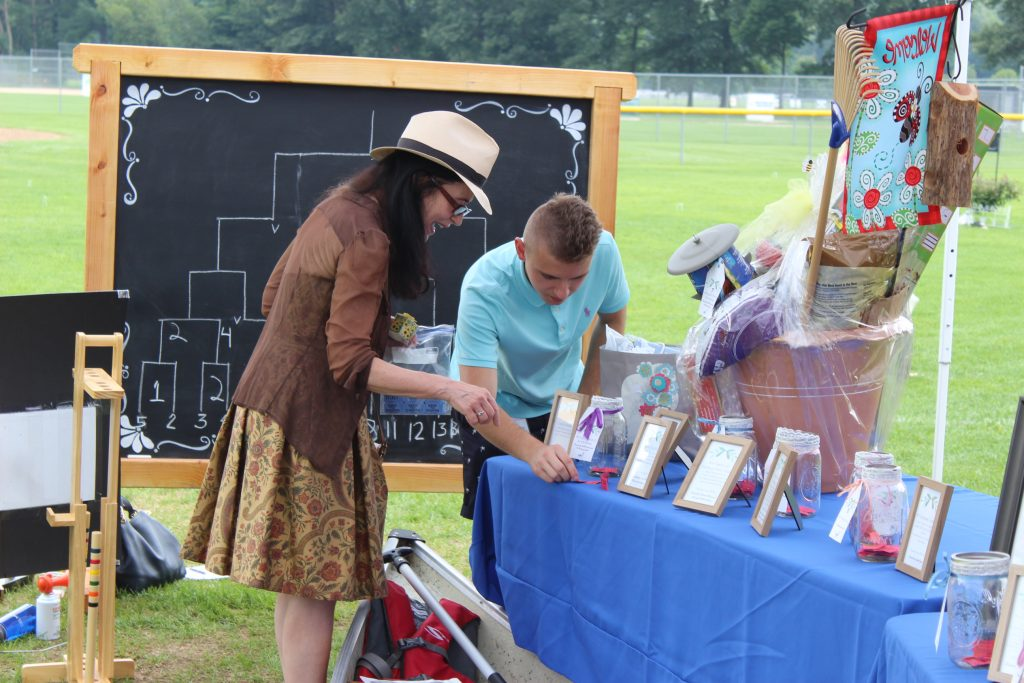 Two people looking at raffle tickets at AIM Services Croquet on the Green event