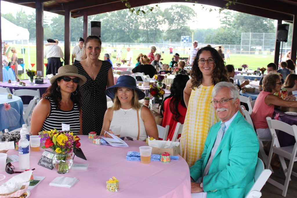 Group of people sitting at table with raffle tickets at AIM Services Croquet on the Green event