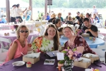Three woman sitting at a table smiling at the camera at AIM Services Croquet on the Green event