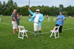 Man in teal jacket and white hat holding croquet mallet in the air at Croquet on the Green 2019