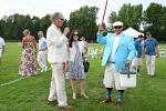 Man in teal coat and white hat holding mallet in the air with a cooler in the other hand as Walt Adams speaks into a microphone at Croquet on the Green 2019