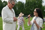 Natalie Sillery speaking into a microphone looking at Walt Adams at Croquet on the Green 2019