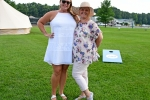Two woman standing together with cornhole set in the background at Croquet on the Green 2019
