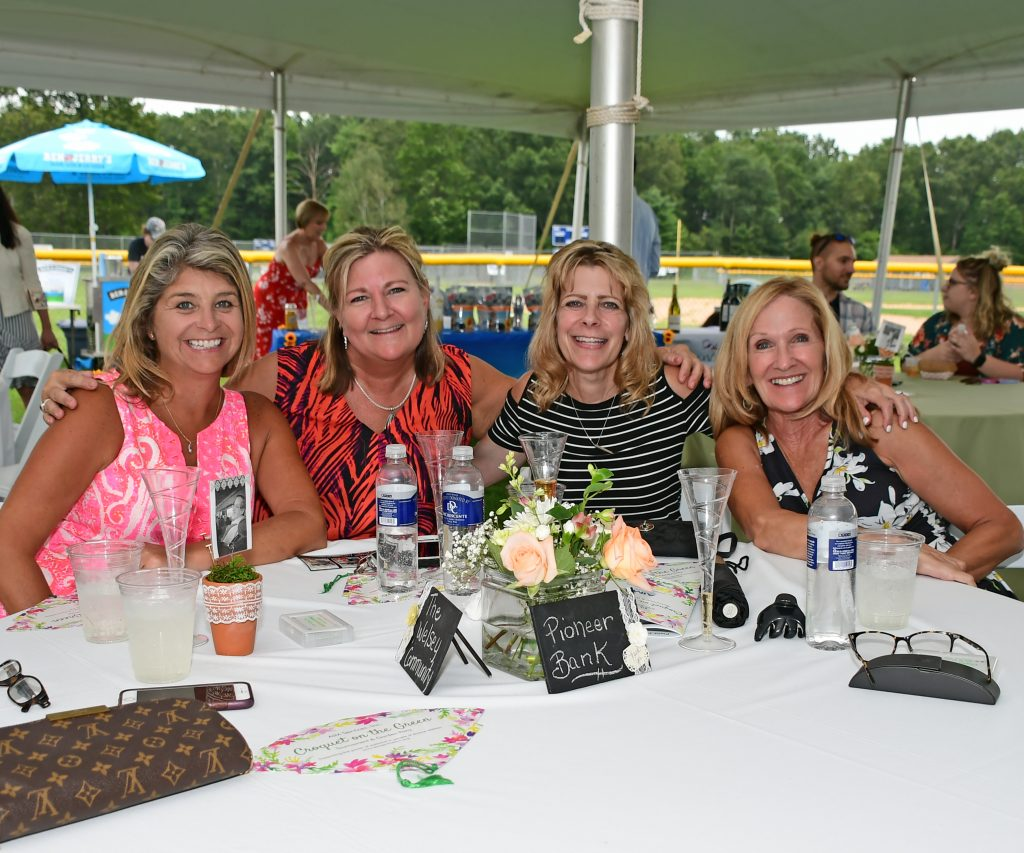 Group of four women at a table smiling at Croquet on the Green 2019