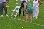 Woman in green dress bent over to hit croquet ball at Croquet on the Green 2019