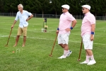 Two men in matching outfits standing watching croquet at Croquet on the Green 2019