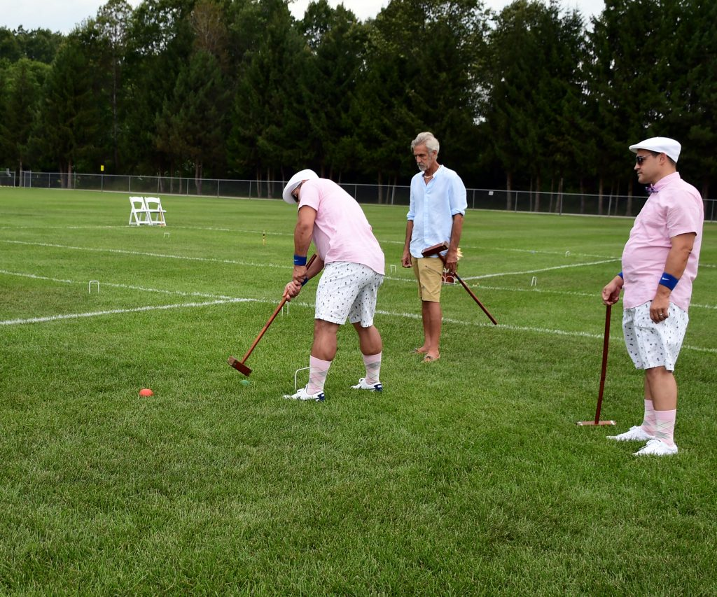 Man hitting croquet ball while two people watch at Croquet on the Green 2019