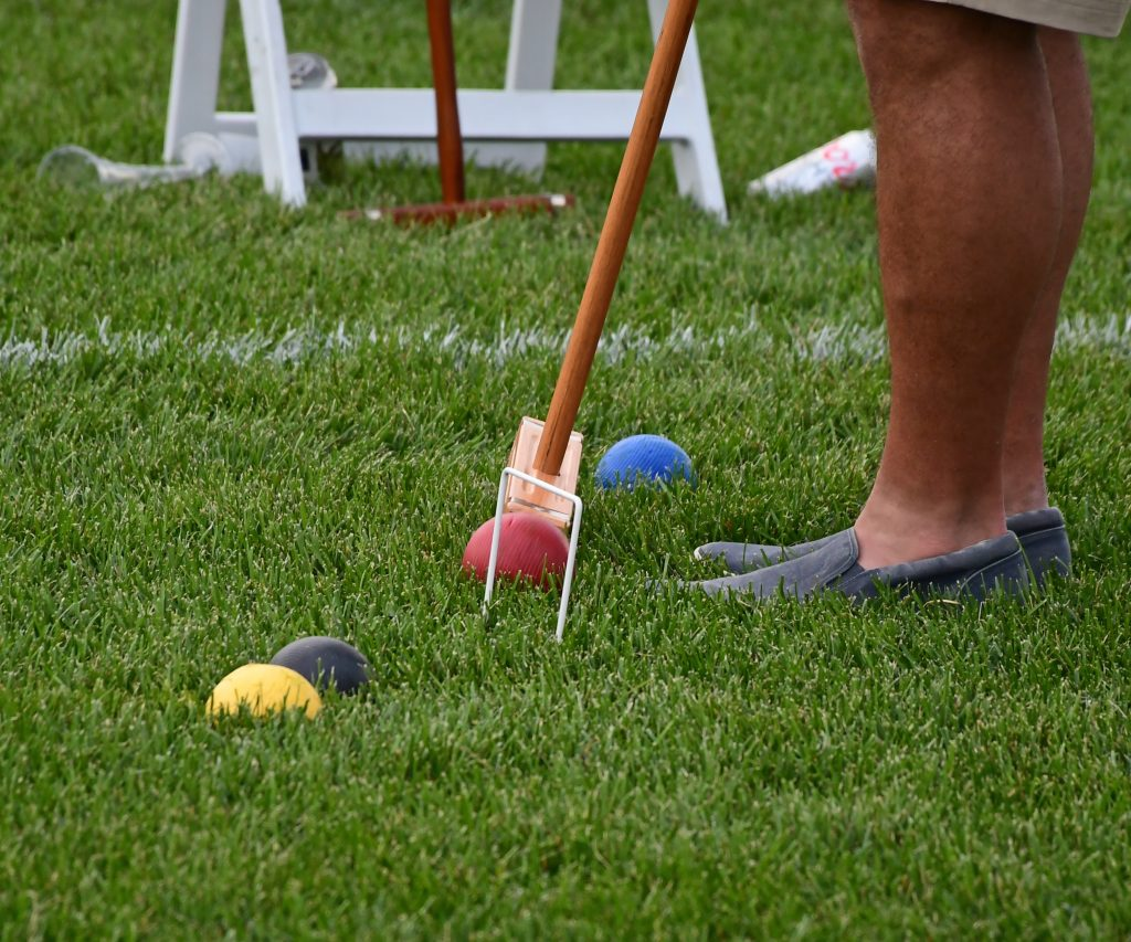 Close up of a mallet hitting a ball at a wicket at Croquet on the Green 2019