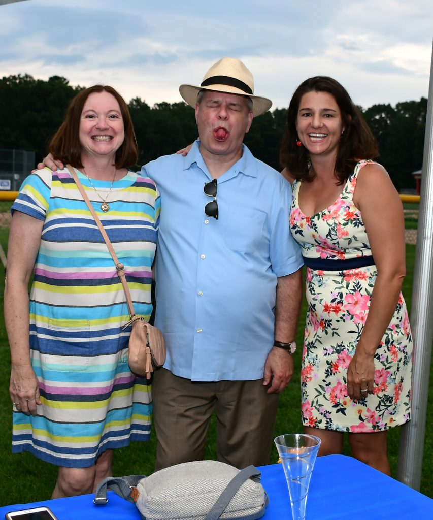 Group of three people with the man in the middle sticking his tongue out at Croquet on the Green 2019