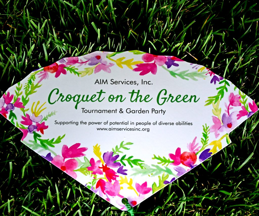 Croquet on the Green fan with flowers on the edges in the grass at Croquet on the Green 2019