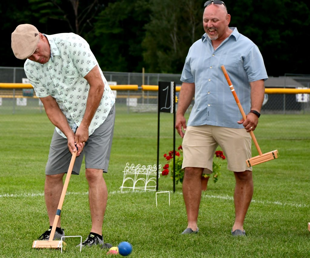 Man hitting croquet ball as another man looks on at Croquet on the Green 2019