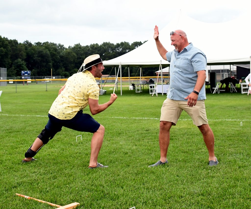 Two men excitedly lining up a high five at Croquet on the Green 2019