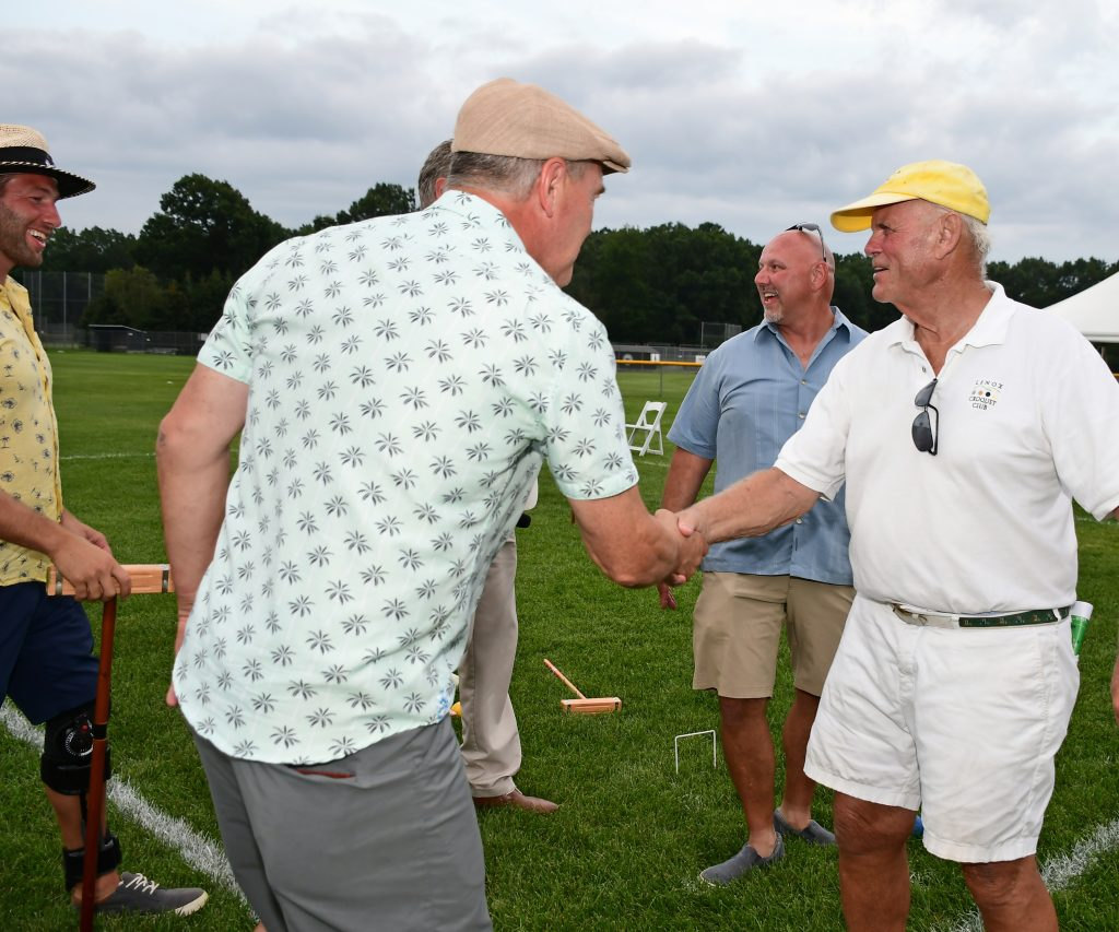 Men shaking hands at Croquet on the Green 2019