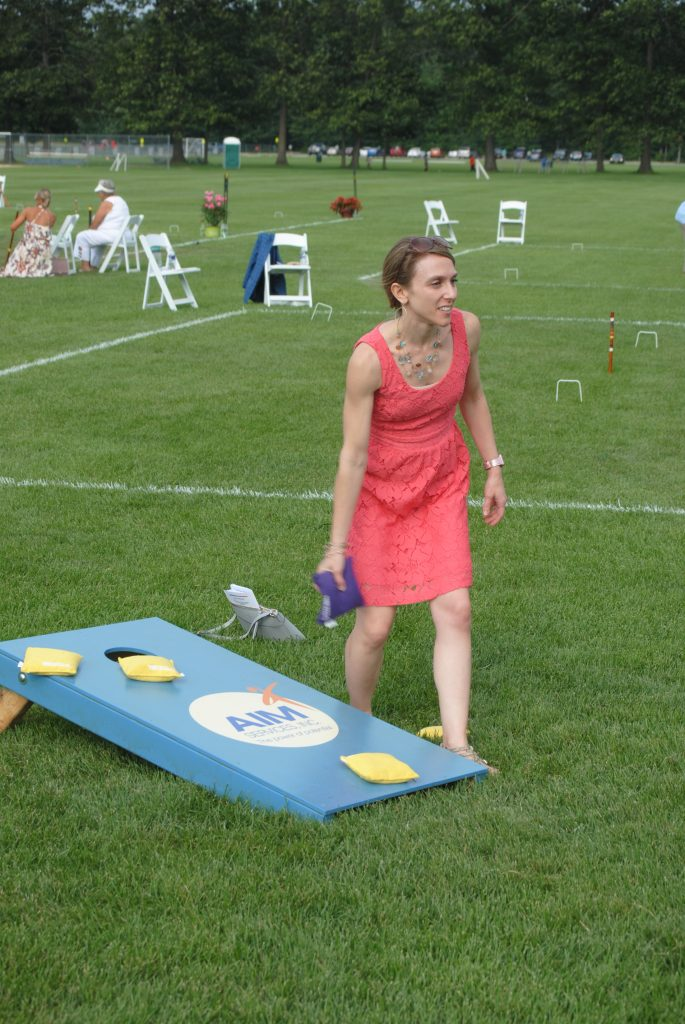 Woman throwing bag at cornhole at Croquet on the Green 2019
