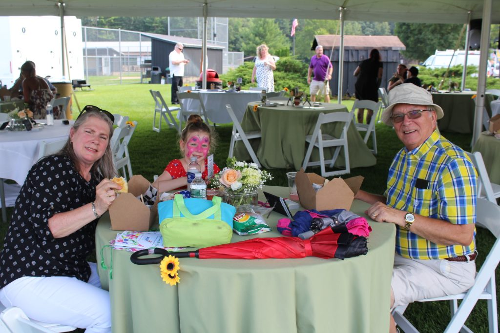 Couple with granddaughter at table at Croquet on the Green 2019