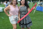 AIM staff Meghan Montayne and Sarah Papenhausen posing with a long strip of red raffle tickets at Croquet on the Green 2019