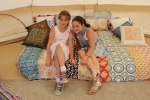Two young girls sitting on a bed with a patchwork pattern blanket in the glamping tent at Croquet on the Green 2019