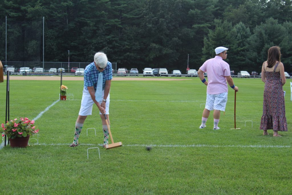 Man in bright plaid shirt with knee high socks with birds on them hitting a croquet ball with a mallet at Croquet on the Green 2019