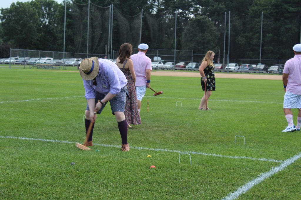 Man bent over hitting croquet ball backwards at Croquet on the Green 2019