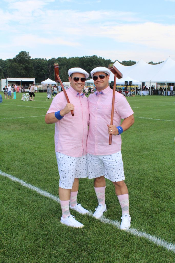 Two men in matching pink shirts, white pattern shorts, pink argyle socks, and white hats at Croquet on the Green 2019