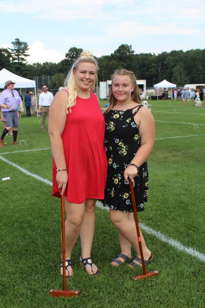 Girl in red dress and girl in black dress with flowers posing with croquet mallets at Croquet on the Green 2019