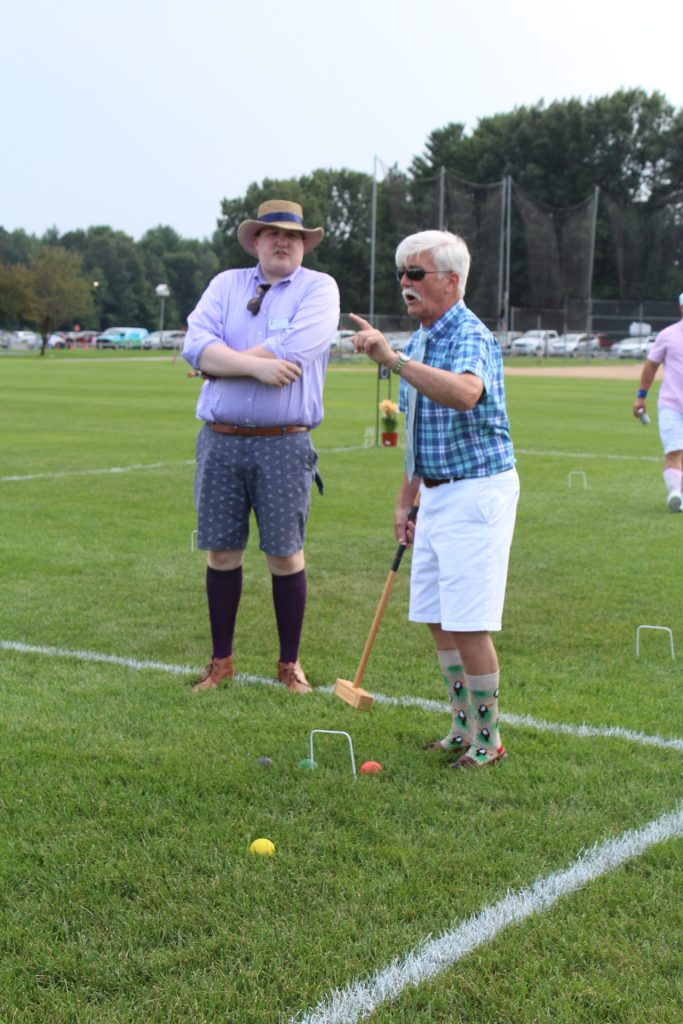 Man in plaid shirt and knee high socks with birds on them pointing and talking while holding a croquet mallet at Croquet on the Green 2019