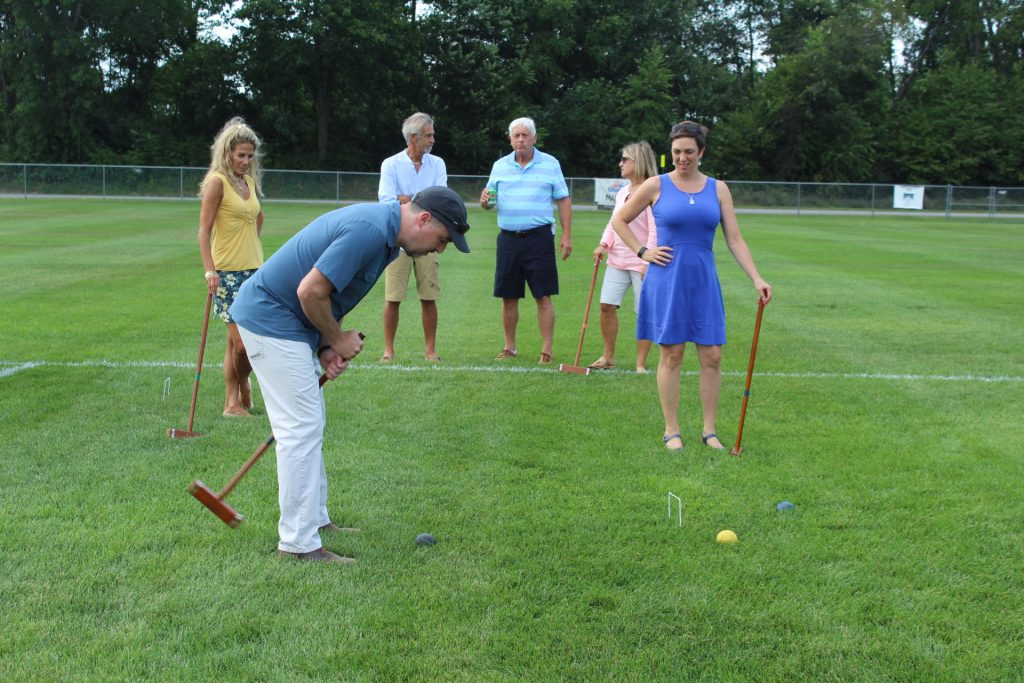 Larry Novik of Bonacio hitting croquet ball while friends look on at Croquet on the Green 2019