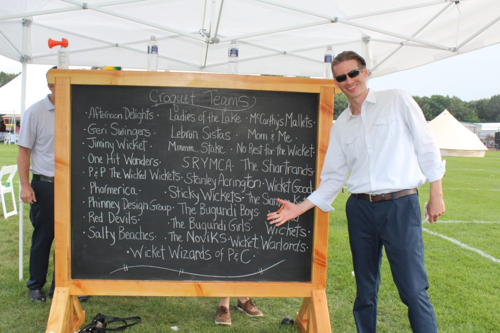 "Man standing in front of and presenting large chalkboard sign that reads croquet team names like ""afternoon delights"" and ""wicket good"""