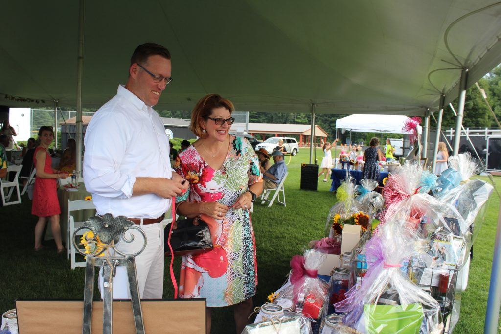 Man and woman with raffle tickets smiling at raffle baskets at Croquet on the Green 2019