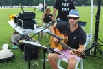 Thomas Powers looking at the camera singing while holding a guitar at Croquet on the Green 2019