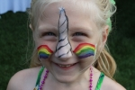 Young blonde girl with unicorn horn and rainbow face paint at Croquet on the Green 2019